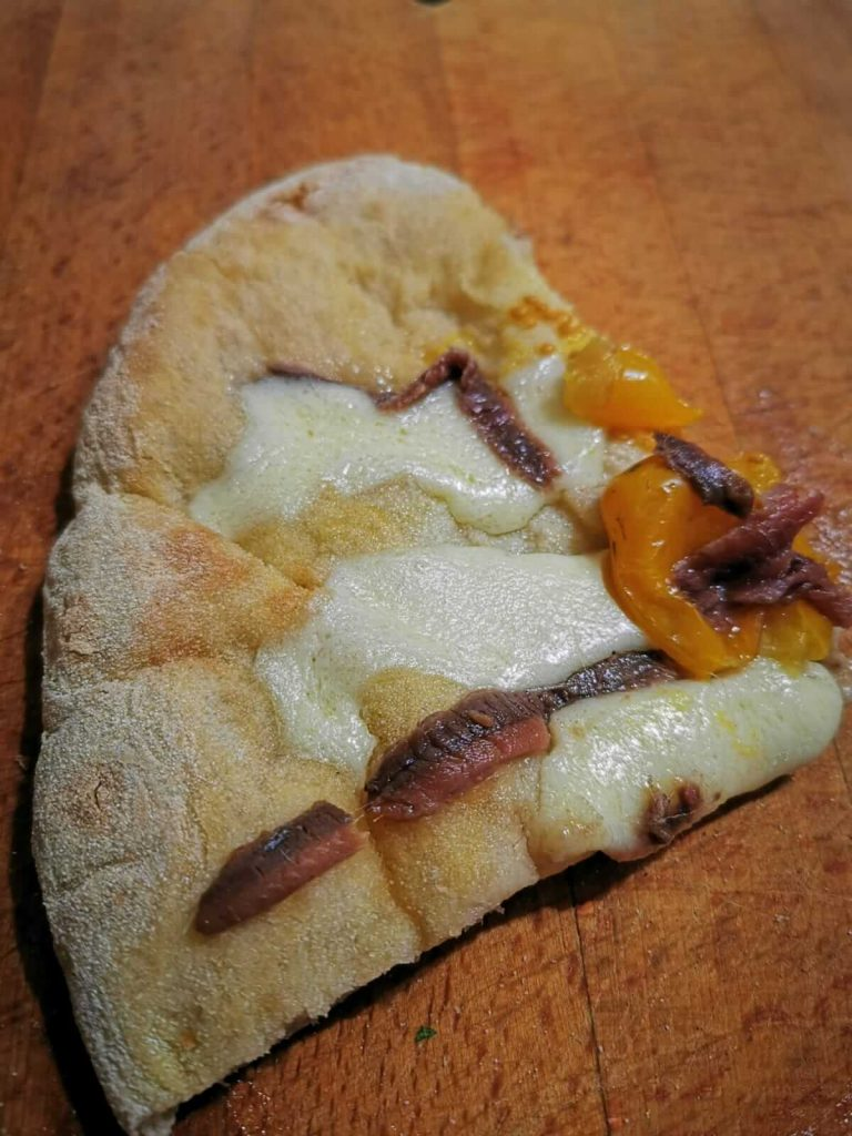 fetta di pizza alici e pomodori gialli